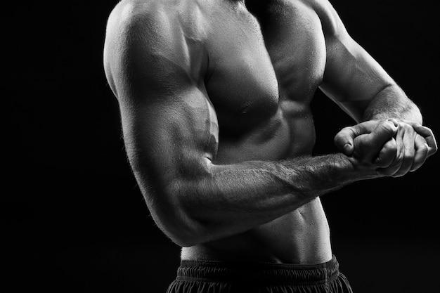 Het kleurloze beeld van de romp van aantrekkelijke mannelijke bodybuilder op zwarte studio achtergrond.