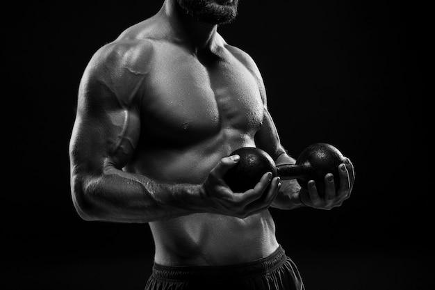 Het kleurloze beeld van de torso van aantrekkelijke mannelijke lichaamsbouwer met gewicht op zwarte studioachtergrond.