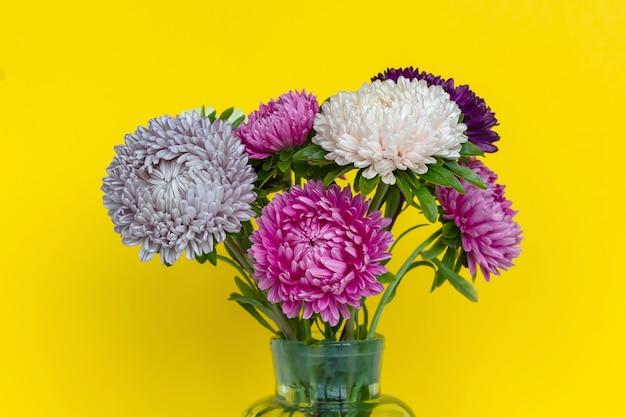Het kleurrijke boeket van astersbloemen in glasvaas.