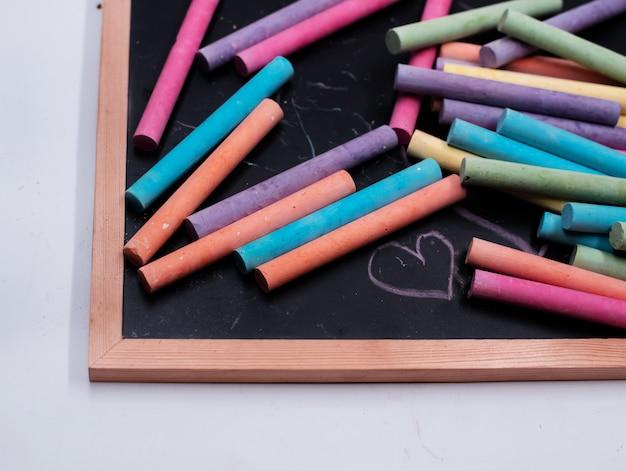 Het kleurrijke krijt zet op blackboard, wazig licht rond