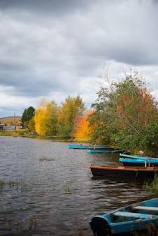 Het kleurrijke landschap van de herfst, meer met botenbomen en kleurrijke bladeren, plattelandsgebied in rusland