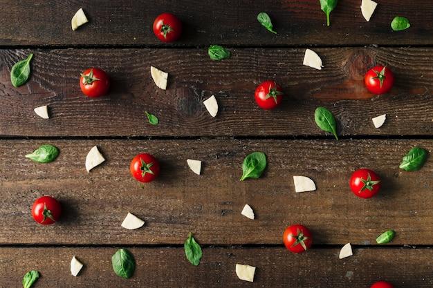 Het kleurrijke patroon van pizza-ingrediënten dat van kerstomaatjes, basilicum en kaas op houten muur wordt gemaakt. koken concept.