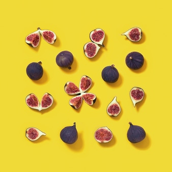 Het kleurrijke verse patroon van het vijgenfruit dat in vierkant op heldergele achtergrond, geheel en gesneden fig. wordt ingeschreven.