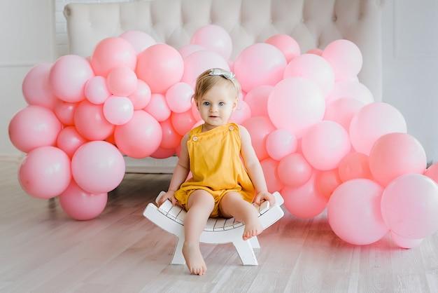Het knappe babymeisje met gouden haar kleedde gele kruippakjezitting op kleine witte bank. gelukkige momenten, roze ballonnen. schattige en mooie kleine jongen, eerste verjaardag.