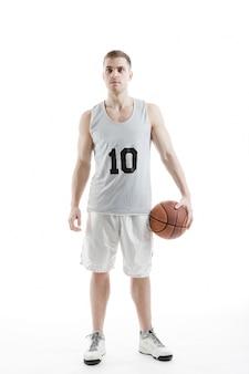 Het knappe basketbalspeler poseren met bal