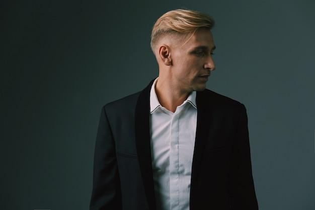 Het knappe blonde jonge mens stellen bij studio