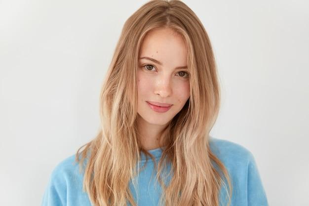 Het knappe blonde jonge vrouwenmodel met licht steil lang haar, heeft gelaatsuitdrukking