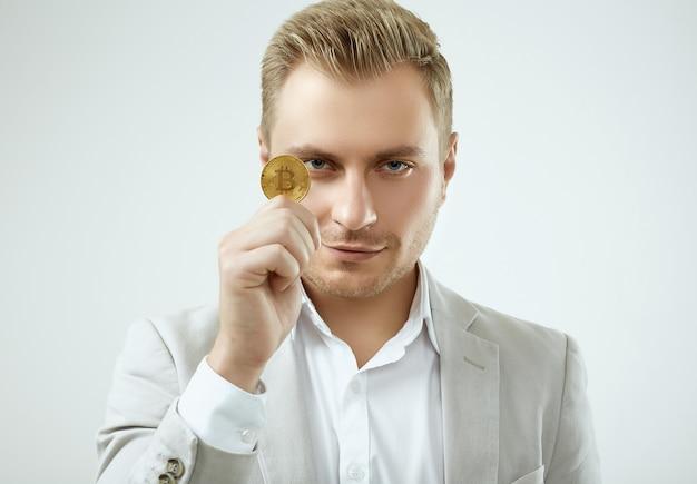 Het knappe blonde mensenmodel in een manier grijs kostuum houdt een bitcoin