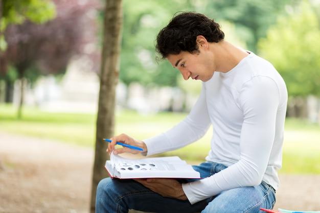 Het knappe boek van de jonge mensenlezing op bank in het park