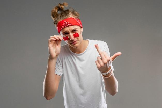 Het knappe emotionele tienerjongen stellen in studio tegen grijs, kerel in een grijs t-shirt en rode zonnebril trekt grimassen en toont de middelvinger