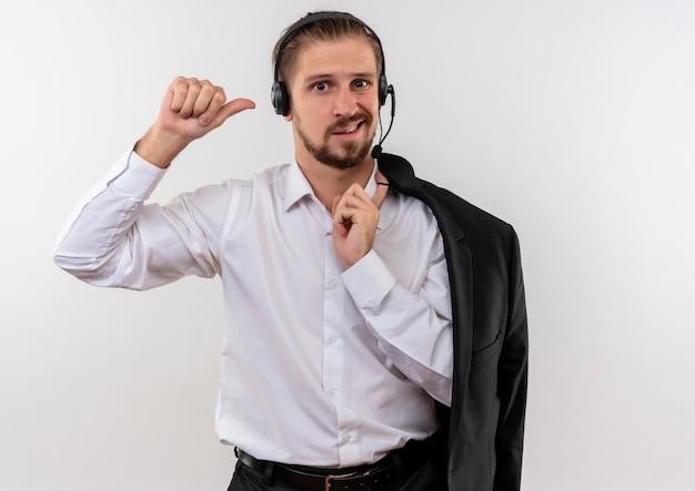 Het knappe jasje van de zakenmanholding over schouder met hoofdtelefoons met een microfoon die camera bekijkt verward die zich over witte achtergrond bevindt