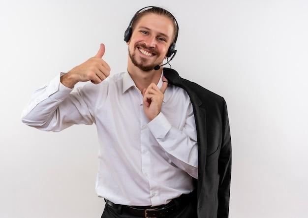 Het knappe jasje van de zakenmanholding over schouder met hoofdtelefoons met een microfoon die camera met glimlach op gezicht bekijkt die duimen op witte achtergrond toont