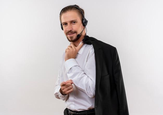Het knappe jasje van de zakenmanholding over schouder met hoofdtelefoons met een microfoon die camera met zekere glimlach bekijkt die zich over witte achtergrond bevindt