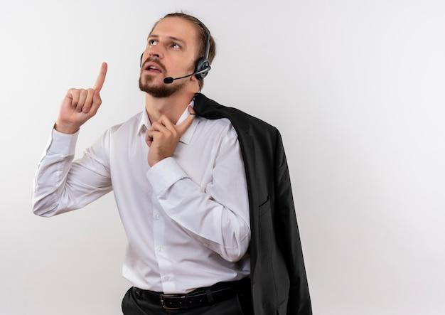 Het knappe jasje van de zakenmanholding over schouder met hoofdtelefoons met een microfoon die met wijsvinger omhoog kijkt die zich over witte achtergrond bevindt