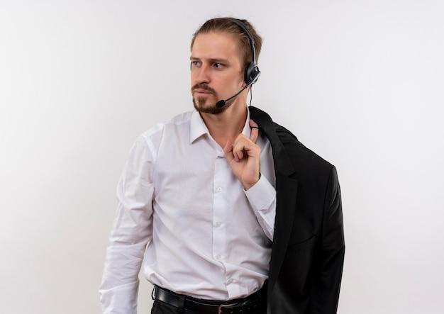 Het knappe jasje van de zakenmanholding over schouder met hoofdtelefoons met een microfoon die opzij met ernstig gezicht kijken dat zich over witte achtergrond bevindt