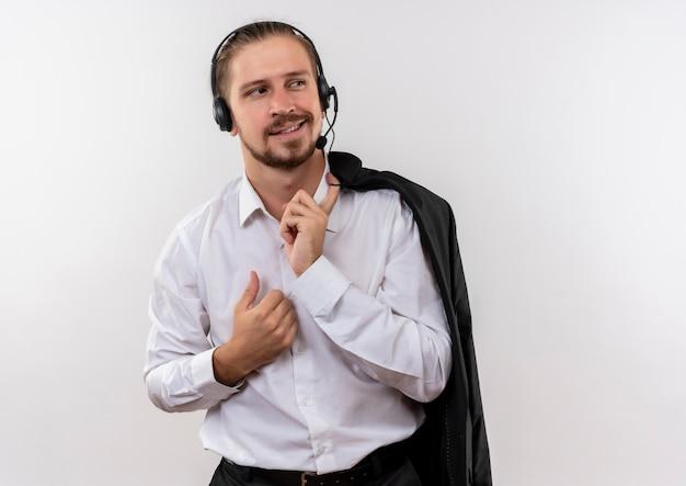 Het knappe jasje van de zakenmanholding over schouder met hoofdtelefoons met een microfoon die opzij met zekere glimlach kijken die zich over witte achtergrond bevindt