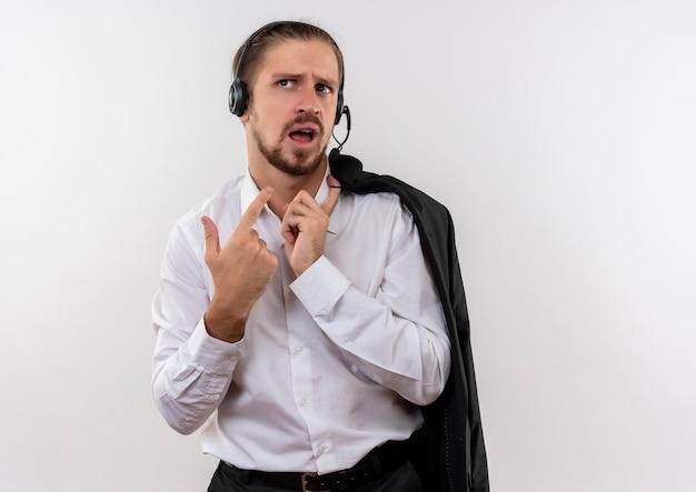 Het knappe jasje van de zakenmanholding over schouder met hoofdtelefoons met een microfoon die opzij verward status over witte achtergrond kijken