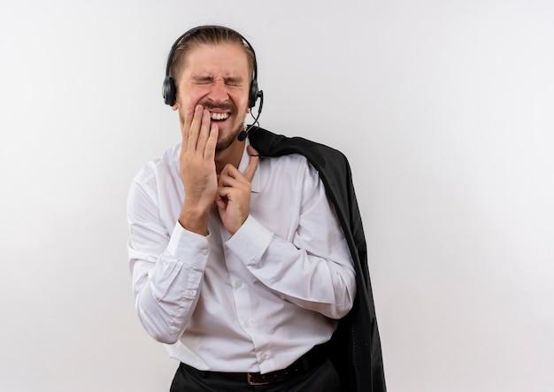 Het knappe jasje van de zakenmanholding over schouder met hoofdtelefoons met een microfoon wat betreft wang met kiespijn die zich over witte achtergrond bevindt