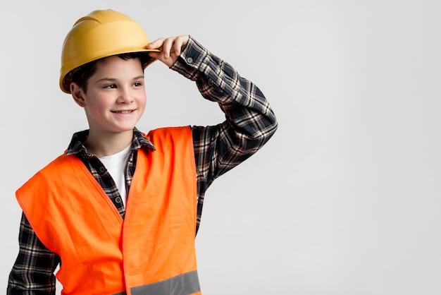 Het knappe jonge jongen stellen met bouwvakker