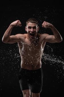 Het knappe jonge mens stellen met waterplonsen op gezicht en borst in studioschot