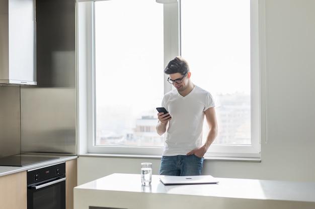 Het knappe jonge mens texting met zijn smartphone in keuken