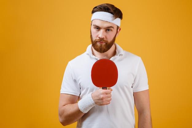 Het knappe jonge racket van de sportmanholding voor pingpong