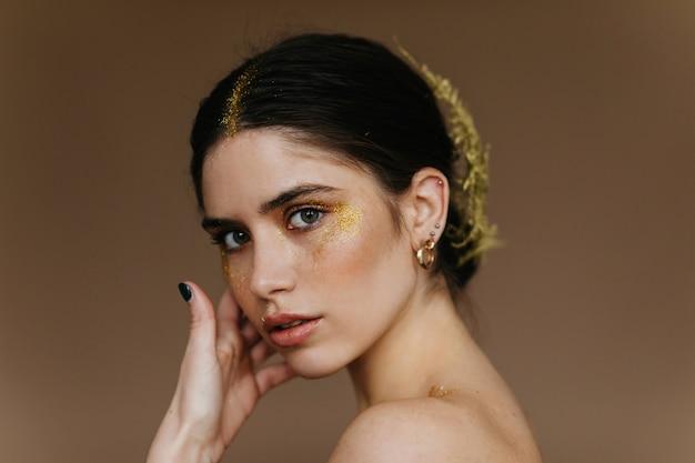 Het knappe jonge vrouw stellen. betoverend meisje in gouden oorringen die zich op donkere muur bevinden.