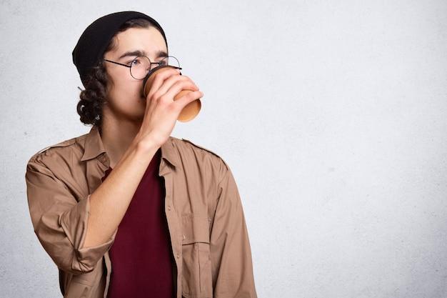 Het knappe mannetje voelt dorstig, drinkt koffie uit document kop, draagt casual t-shirt en hoed, die over wit wordt geïsoleerd