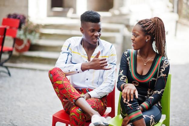 Het knappe modieuze afrikaanse amerikaanse paar stelde samen op straat bij liefdezitting bij lijst openluchtkoffie.