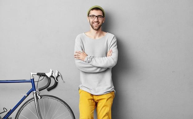 Het knappe positieve gebaarde jonge mensenfietser stellen bij grijze blinde muur met copyspace