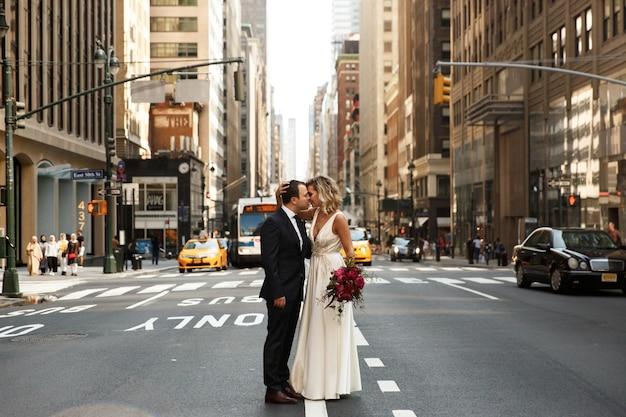 Het knuffelen van pasgetrouwden staat in het midden van de straat in de stad new york