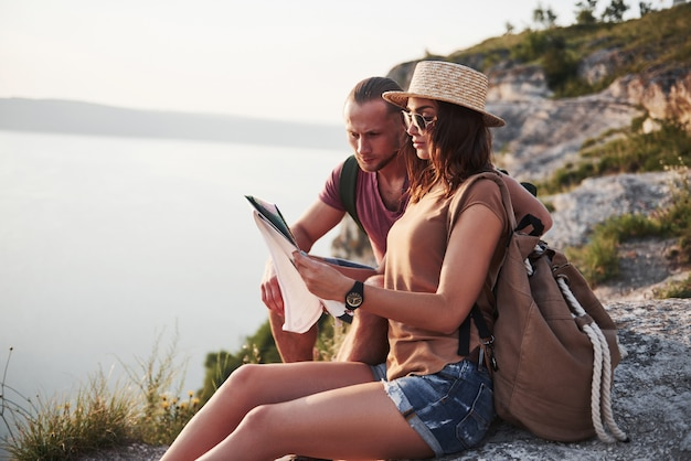 Het koesteren van paar met rugzakzitting bovenop rotsberg die van meningskust een rivier of een meer geniet. reizen langs bergen en kust, vrijheid en actieve levensstijl concept