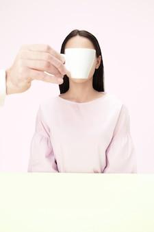 Het koffiepauze-concept. vrouw voordat het drinken van koffie zit binnen aan tafel in de studio.