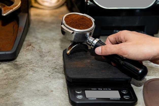 Het koffiezetapparaat weegt de gebrande koffie die is geplet om de basis volgens het recept te verkrijgen