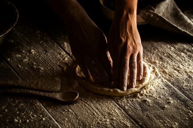 Het koken van bakkerijhanden verfrommelt deeg in vlakke cake