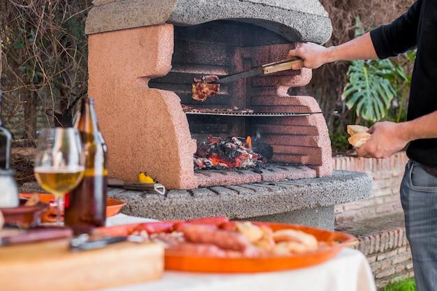 Het koken van de mens vleeslapjes vlees bij de grill in openlucht