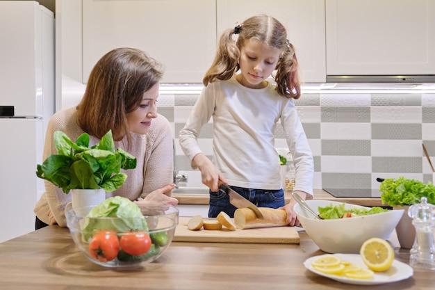 Het koken van de moeder en van de dochter samen in de keuken thuis