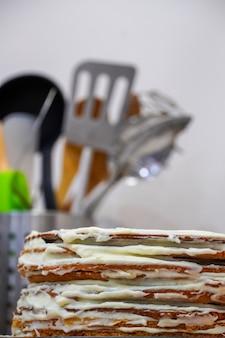 Het koken van een feestelijke meerlagige verjaardagstaart op een achtergrond van bestek. scones en slagroom. een laag bananencake leggen voor sappige taart.