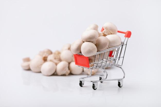 Het kopen van gezond voedselconcept. winkelwagentje met champignons op grijze achtergrond.