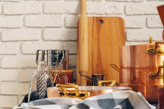 Het koper cookware met houten keukengerei sluit omhoog