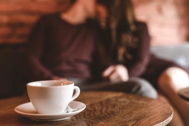 Het kopje koffie op de achtergrond van het kussende paar