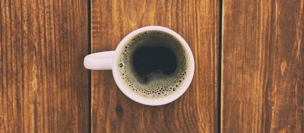 Het kopje koffie op de houten vloer
