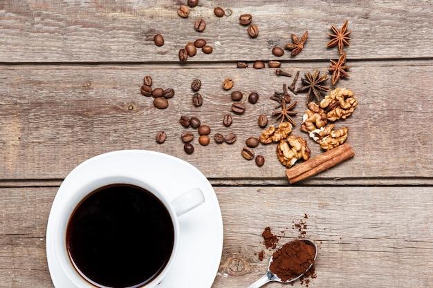 Het kopje koffie op houten tafel met koffiebonen, noten, kaneelstokje