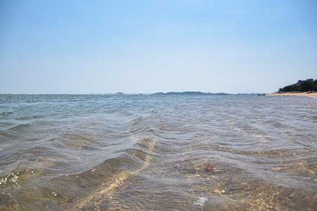 Het kristalheldere zeewater ligt in de zomer op het strand