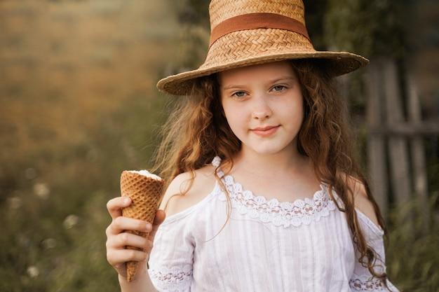 Het krullende meisje in een strohoed eet roomijs in het dorp in de zomer