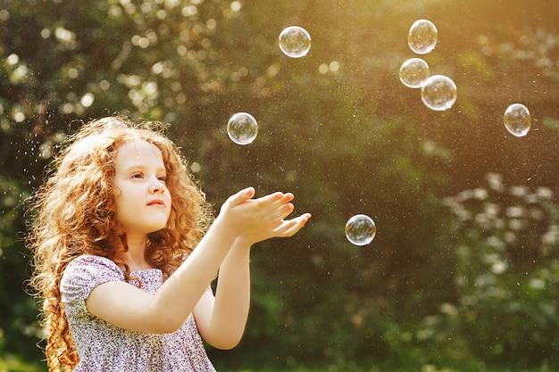 Het krullende meisje vangt zeepbels.