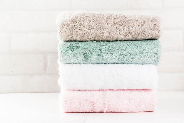 Het kuuroord ontspant en badconcept, stapel schone badhanddoeken kleurrijke katoenen badstoftextiel