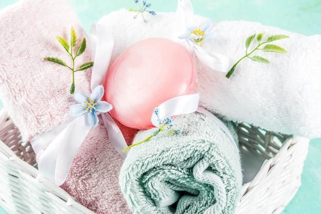 Het kuuroord ontspant en badconcepten overzeese zoute zeep met schoonheidsmiddelen en handdoeken op lichtblauwe conreteachtergrond
