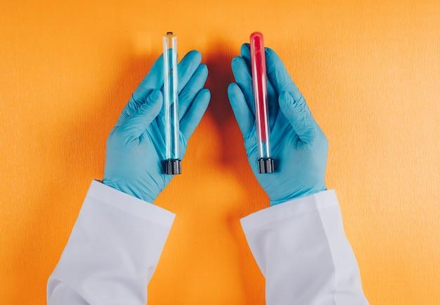 Het laboratoriumflesjes van de artsenholding in beide handen op sinaasappel