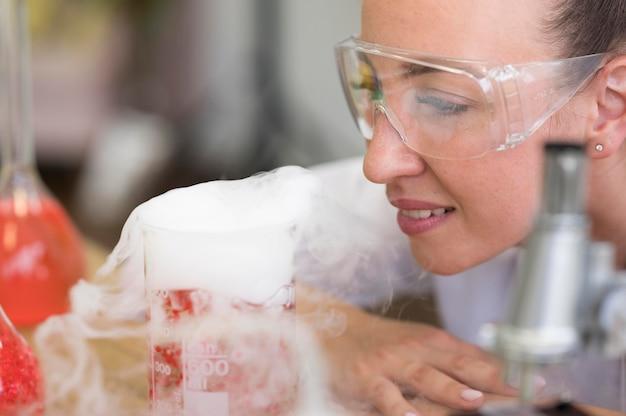 Het laboratoriumvrouw van de close-up met glazen